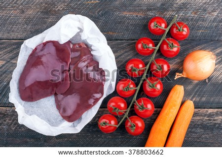 Liver and vegetables tomatoes, carrots and onion on rustic wooden background. Ingredients for liver or pate. Top view - stock photo