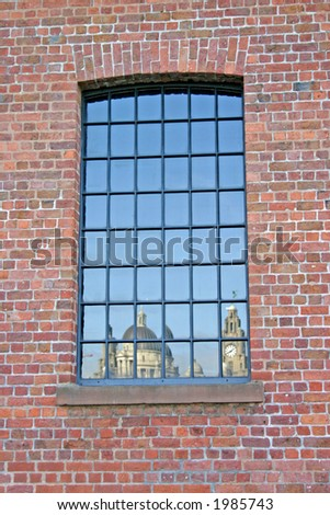 Liver Building  and 3 Graces Reflected in Warehouse Window in Liverpool UK - stock photo