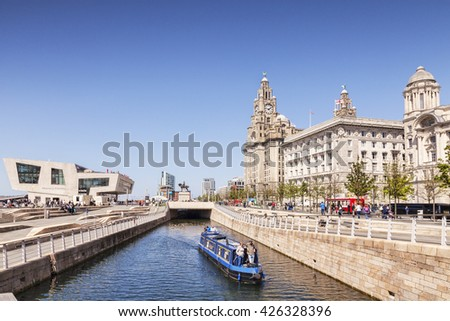 Liverpool, England: 14 May 2016 - A narrowboat passing through the Liverpool Canal Link, in front of the Three Graces and the Mersey Ferries Building, Liverpool, England, UK