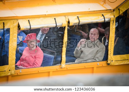 LIVERPOOL, ENGLAND - MAY 17: Her Royal Highness Queen Elizabeth II and the Duke of Edinburgh on the Yellow Duckmarine in Liverpool during the Diamond Jubilee tour, Liverpool, England. May 17, 2012 - stock photo