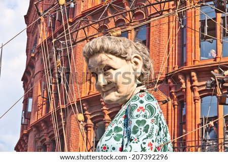 "LIVERPOOL, UK - JULY 25, 2014: The giant ""Grandma"" puppet walks the streets of Liverpool during 'Memories of 1914' - an event in the city as part of the World War I centenary commemorations. - stock photo"