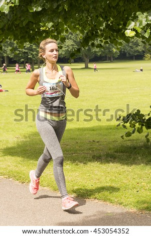 Liverpool, UK - June 26, 2016: Race for Life sponsored fun run for British charity Cancer Research UK. Woman undertaking her run  - Editorial