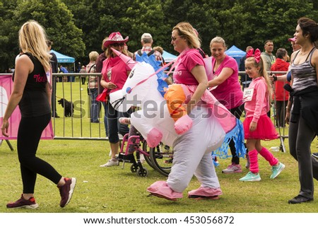 Liverpool, UK - June 26, 2016: Race for Life sponsored fun run for British charity Cancer Research UK.  Runners and walker making their way to the start line - Editorial - stock photo