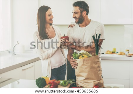 Living a healthy life. Beautiful young couple unpacking shopping bag full of fresh vegetables and smiling while standing in the kitchen together - stock photo