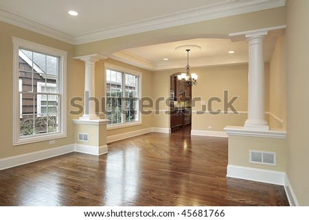 Living and dining room with white pillars in new construction home