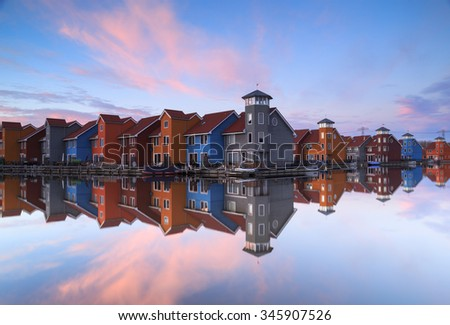 Living at the waterfront: tranquil sunset reflected in a small harbor in the Netherlands. - stock photo