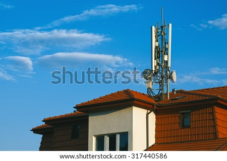 Living building with GSM antennas on roof isolated on blue sky - stock photo