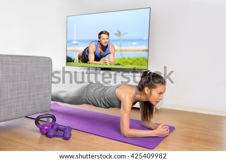 Living room fitness workout - girl doing plank exercises to exercise core at home. Young Asian woman training muscles in front of the TV as part of a healthy lifestyle without going to the gym. - stock photo