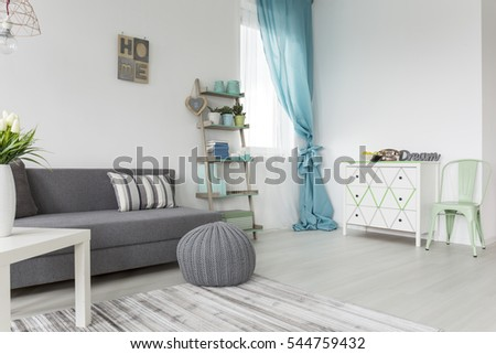 Living Room In Shades Of Gray And Pastel Colors With Sofa Bed, A Dresser And