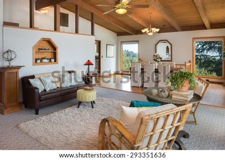 Living room interior beautifully staged with bamboo chairs, rug and view windows. Stunning living room in craftsman home with dramatic wood beamed ceilings. Beautiful craftsman house. - stock photo