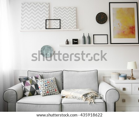 Living room interior, grey couch and shelves with paintings on white wall background - stock photo