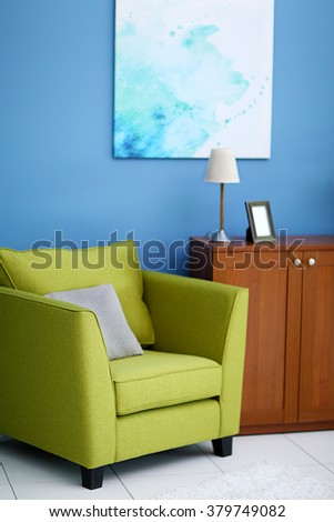 Living room interior with green armchair, commode and picture on blue wall background