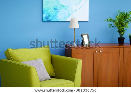 Living room interior with green armchair, commode and picture on blue wall background - stock photo