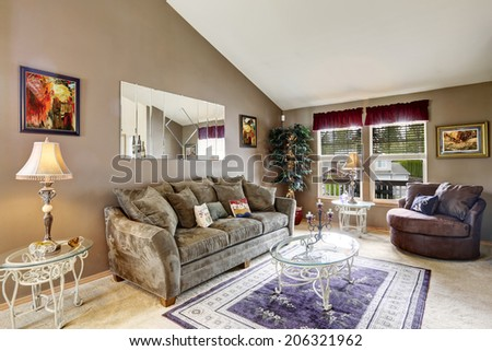 Living room interior with high vaulted ceiling and beige carpet floor. Furnished with olive sofa, brown love seat and glass top tables