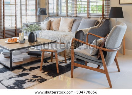 living room interior with pillows on sofa and decorative wooden table with lamp - stock photo