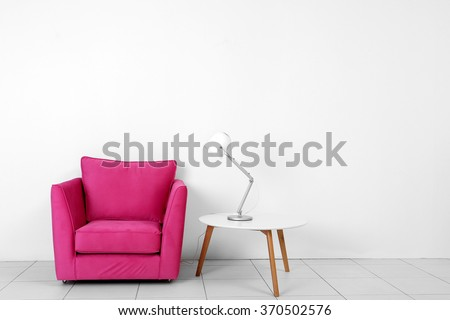Living room interior with pink armchair, white table and lamp  on white wall background - stock photo