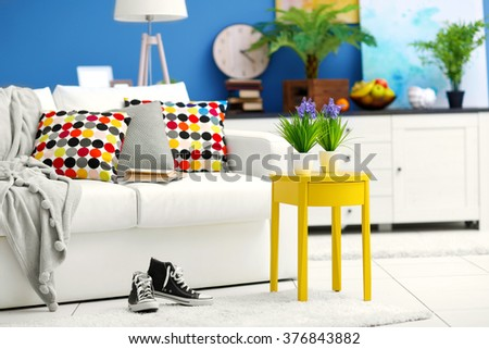 Living room interior with white furniture and green plants on blue wall background