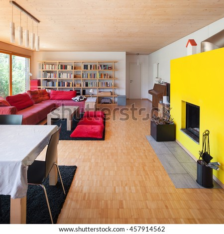 Living room of an eco house, red divan and fireplace - stock photo
