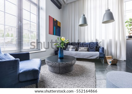 living room with blue upholstered furniture window blinds and white net curtain