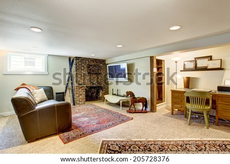Living room with brick background fireplace, old leather couch and small office area - stock photo