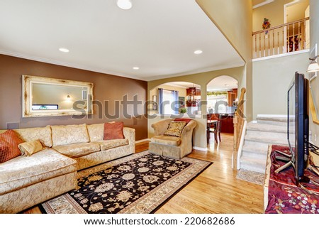 Living room with brown and ivory color walls. Creamy tone sofa with red pillows and armchair. View of kitchen area