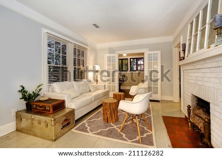 Living room with cozy fireplace. Furnished with antique chests and modern sofa and chairs