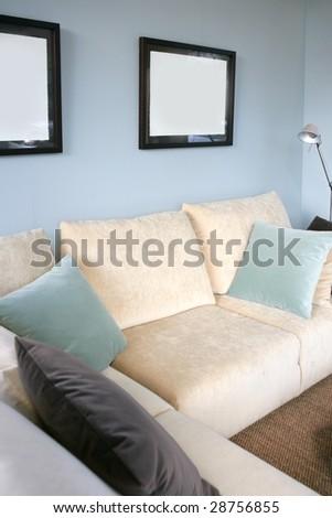 Living room with cream sofa, soft blue wall, interior design - stock photo