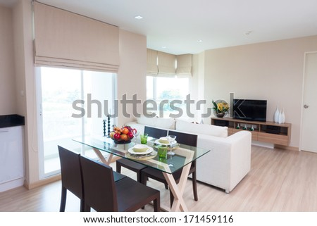 living-room with dining table in condominium. - stock photo