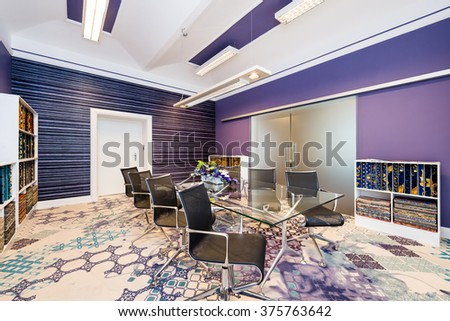 Living room with glass table and blue-violet walls - stock photo