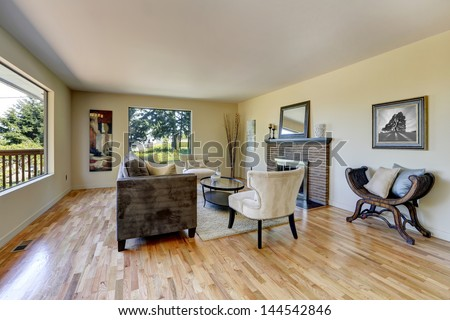 Living room with hardwood floor, fireplace and large windows. - stock photo