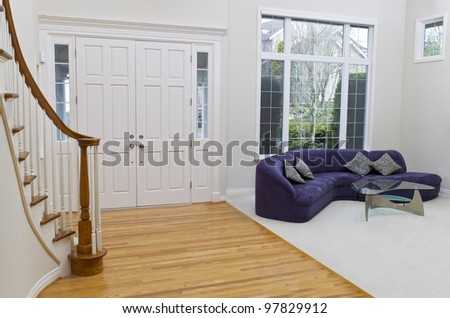 Living room with sofa, glass table, oak and carpet floors with large window in background - stock photo