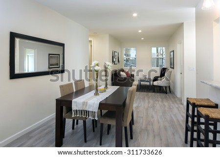 Living room with wooden floor and dining table with mirror and bar chairs. - stock photo