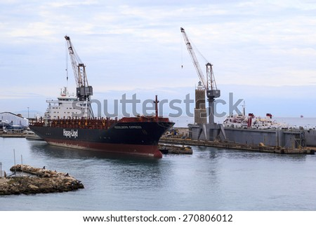 LIVORNO, ITALY - MAY 20, 2014 - The container ship Heidelberg Express awaiting for load. Livorno is one of the busiest cargo port of Italy, also many cruise liner bring visitors into the country. - stock photo
