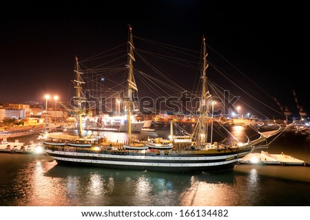 LIVORNO, ITALY - SEPTEMBER 24, 2012 - Well illuminated port of Livorno with old styled wooden ship on the frontage, on September 24, 2012 in Livorno.