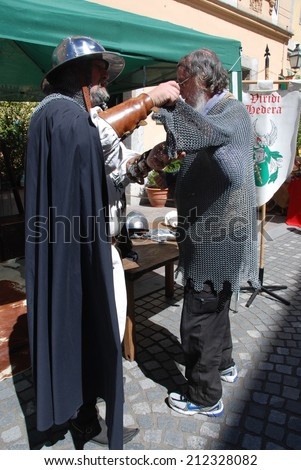 LJUBLJANA, SLOVENIA - AUGUST 17, 2014: Unknown visitor at Medieval Fair try on a suit of mail with help from a member of Society of Knighted Viridi Hedera. Lifestyle in medieval time.