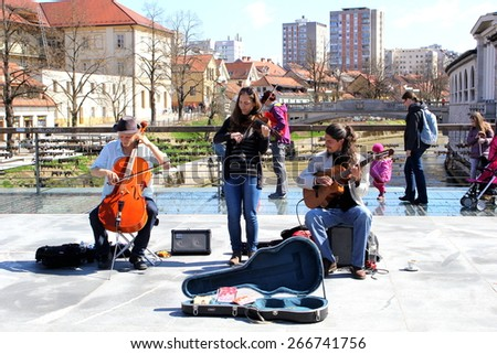 """LJUBLJANA, SLOVENIA-MAR. 28, 2015:  Street musicians perform their music on the pedestrian """"lock bridge"""" for passing locals on a sunny weekend in the nation's capital. - stock photo"""