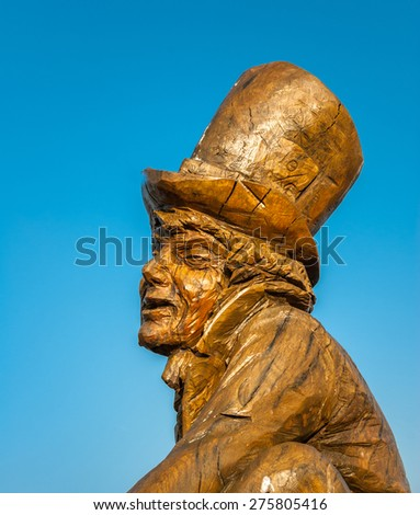 LLANDUDNO April 9th 2015. A carved wooden statue of Lewis Carrol's Mad Hatter from  Alice in Wonderland. Sculpted by Simon Hedger who marks the link between the author and the town. - stock photo