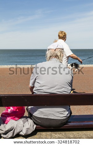 Llandudno, Wales, UK - May 17, 2014: Elderly man protects his balding head with a knotted handkerchief from the hot sunshine whilst sitting on wooden bench on Llandudnos north promenade in Wales U.K  - stock photo