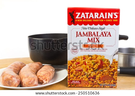 LLANO, TEXAS-FEB 06, 2015: Jambalaya Meal by Zatarain's needs only water and choice of meat - sausage in this case.  Cooking utensils on wooden cutting board against white background with copy space.  - stock photo