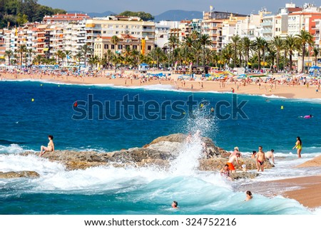 Lloret de Mar, Spain - September 13 2015: A crowd of vacationers enjoy the warm beaches of the Costa Brava in Lloret de Mar. Lloret de Mar is one of the largest resorts on the coast of Spain.