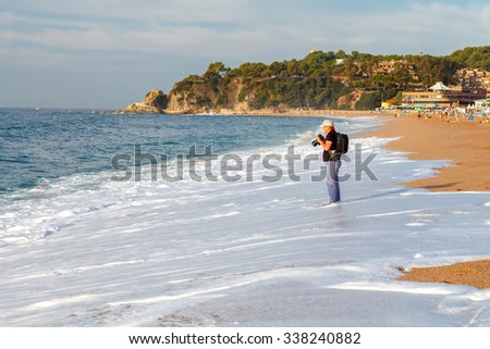 Lloret de Mar, Spain - September 13, 2015: A woman photographs the sea on the beach in Lorette De Mar. Lloret de Mar is one of the largest resorts on the coast of Spain.