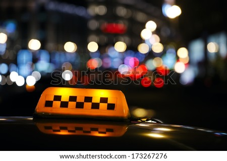 lluminated traditional yellow taxi sign on top of a cab in a city street with a colourful bokeh of urban lights - stock photo