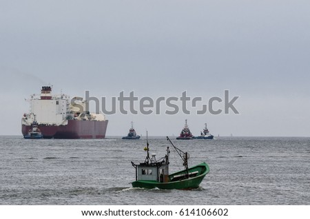LNG TANKER AND FISH BOAT - Tugboats assists on a big ship sailing on a cruise