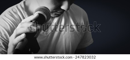 lo-key B&W emotion portrait of asian male singer hold microphone & copy space isolated - stock photo
