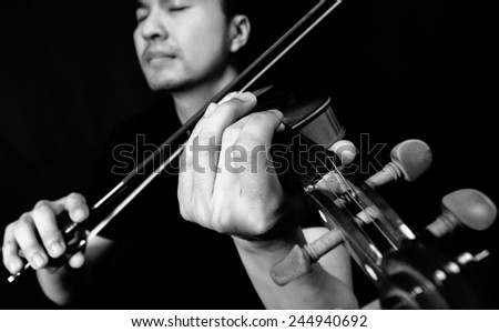 lo-key image of asian handsome violinist musician plays old vintage classical violin on black , focus to left hand / black and white processed - stock photo
