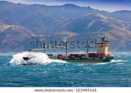 Loaded container freighter ship sailing in stormy ocean with tall and heavy breakers still near shore - stock photo