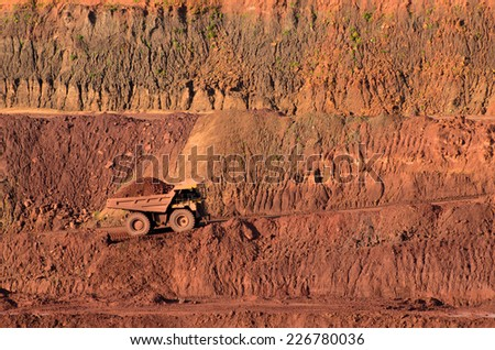 Loaded tip-truck going up along the open mine wall - stock photo