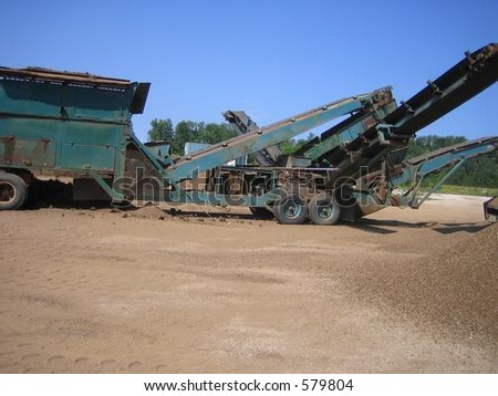 Loader and crusher on site at gravel pit - stock photo