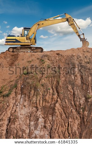 loader excavator in open sand mine over scenic blue sky - stock photo