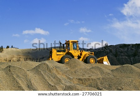 Loader in gravel pit with blue sky - stock photo